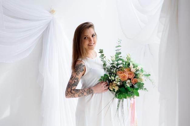 Красивая беременная девушка в белом платье и с букетом цветов