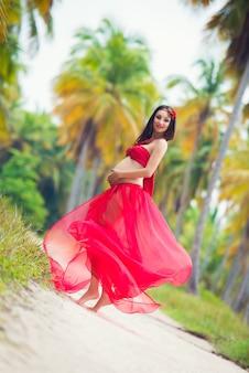 ヤシの木と砂浜の赤いドレスで美しい妊娠中の女の子