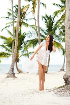 ヤシの木の近くのビーチで白いドレスとつばの広い帽子の美しい妊娠中の女の子