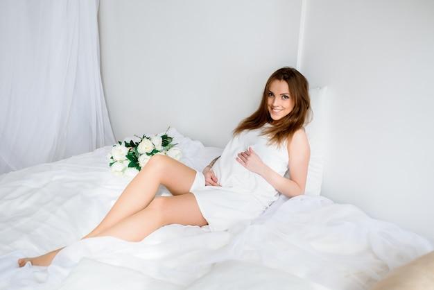 Красивая беременная девушка в белом платье.