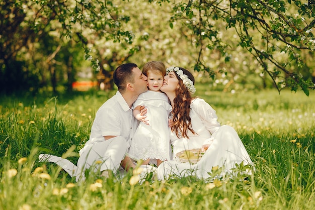 Beautiful pregnant girl in a long white dress with her boyfriend and their little daughter