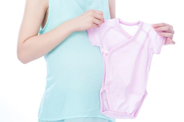 아름다운 임신 한 여자는 당신의 아기 옷을 보여줍니다
