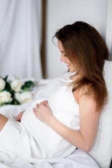 Красивая беременная девушка с зонтиком в белом платье.