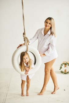 A beautiful pregnant mom plays with her daughter on a swing in a white room