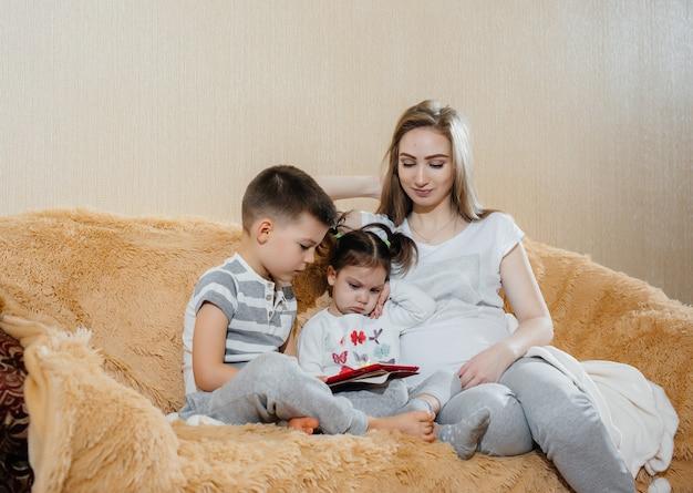 Красивая беременная мама сидит на диване со своим сыном и дочерью и играет планшет