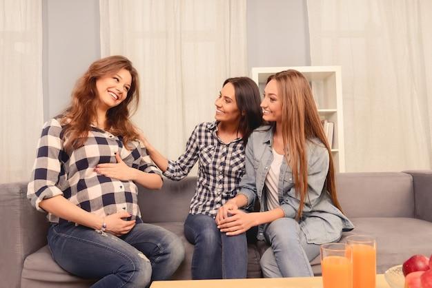 美しい妊婦とソファに座っている彼女の幸せなガールフレンド