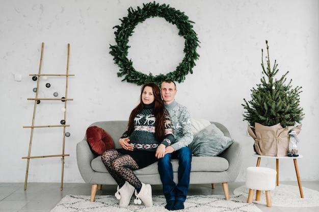 Красивая беременная женщина и мужчина в мягких свитерах на диване возле дерева