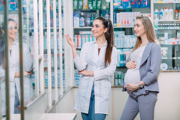 A beautiful pregnant woman consults at a pharmacy.