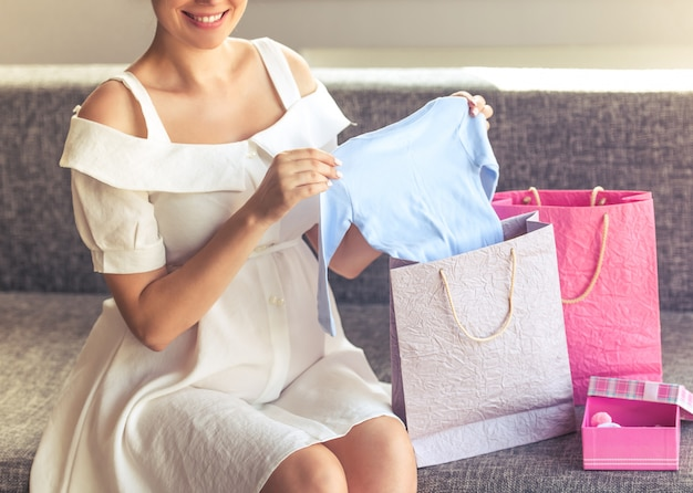 Beautiful pregnant woman in dress holding cute baby clothes.