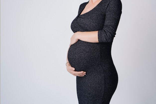Beautiful pregnant woman in a dress standing touching her belly