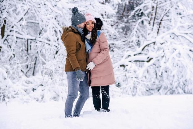 雪の降る冬に彼女の素敵な夫と一緒に歩いて暖かい服を着た美しい妊婦