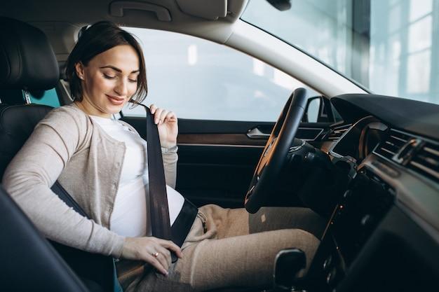 車で運転する美しい妊娠中の女性