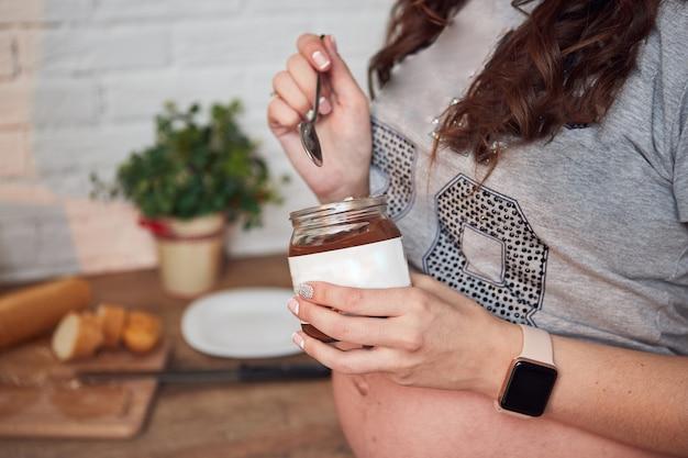 Beautiful pregnant woman enjoying eating chocolate paste