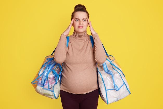 Красивая беременная женщина чувствует схватки, нуждается в помощи и вызывает скорую помощь с испуганным выражением лица, волнуется, держит руки на висках, держит вещи для роженицы.