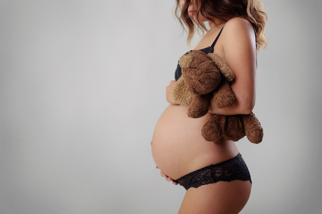 美しい妊娠中の女性は、分離されたスタジオのおなかでおもちゃを保持しています。若い女性は彼女の優しく妊娠したおなかを抱き締めます。将来の母親の待っている子の肖像画。