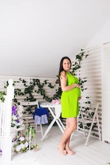 緑のドレスで美しい妊娠中の女性