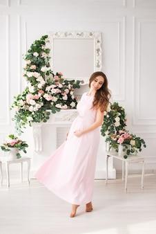 Красивая беременная женщина в светло-розовом платье в светлой студии с цветами