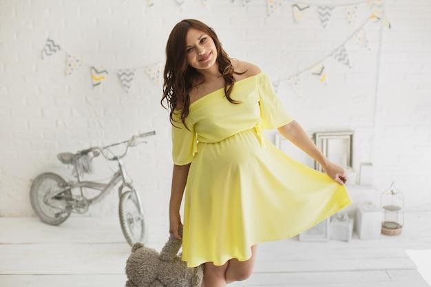 スタジオで黄色いドレスを着た美しい妊婦。