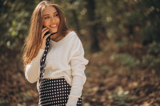秋の公園で美しい妊婦