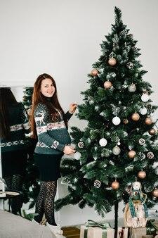 Красивая беременная женщина в уютной одежде возле елки с новым годом и рождеством