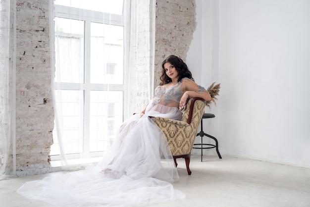 肘掛け椅子に座ってポーズをとってドレスの美しい妊婦