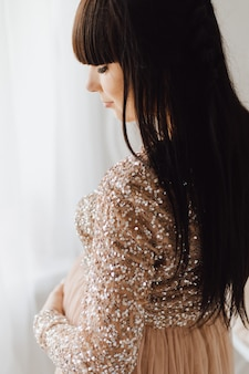 Beautiful pregnant woman in long beige dress standing in a bright cosy room