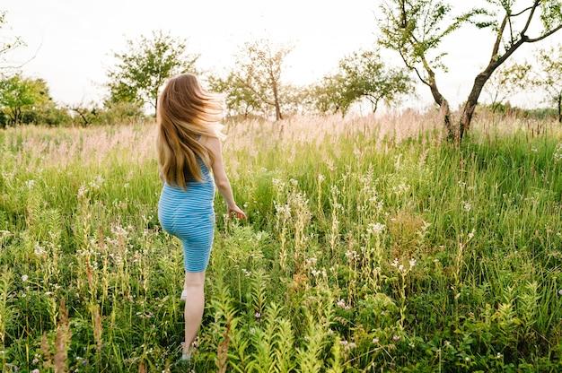 Красивая беременная женщина в стильном летнем платье работает, гуляя в поле с цветами в солнечном свете, наслаждаясь чувством свободы.