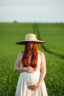 Красивая беременная женщина в белом платье гуляет в зеленом поле