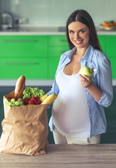 Beautiful pregnant woman is holding an apple.