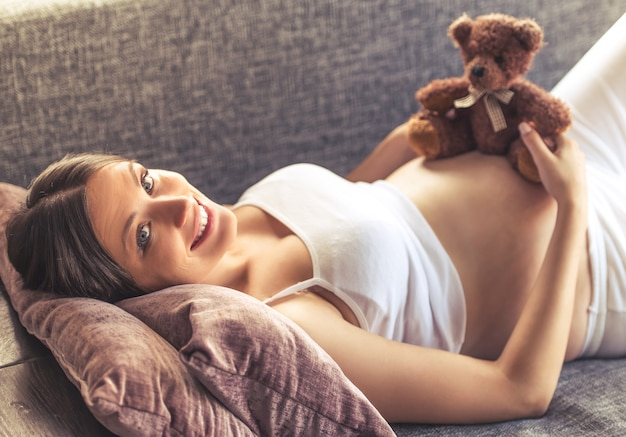 Beautiful pregnant woman is holding a teddy bear.