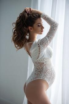 아름 다운 임신 한 여자는 openwork 레이스 흰색 란제리 바디 슈트를 입고 창 근처에 서 있습니다. 소녀는 손으로 긴 물결 모양의 머리카락을 곧게 만듭니다.