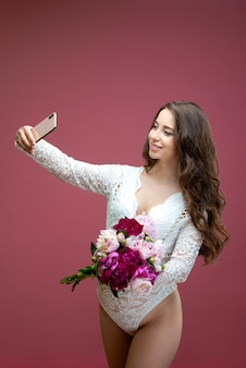 Beautiful pregnant woman in lace white lingerie body suit makes a selfie with a bouquet of flowers peony.