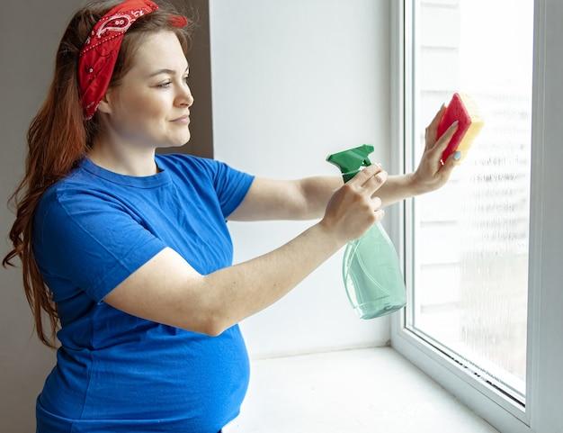 Una bella donna incinta negli ultimi mesi di gravidanza è impegnata nella pulizia e lava i vetri.