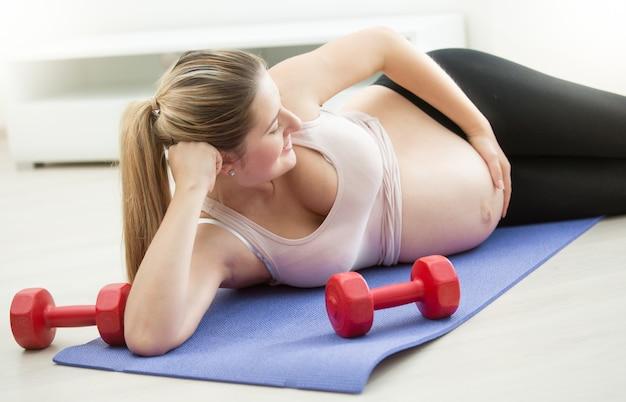 フィットネスマットの上に横たわって、大きなお腹に触れる美しい妊婦