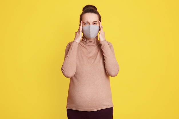 Beautiful pregnant woman in medical face mask keeping fingers on temples, suffering from headache, being scared to get infected of corona virus, wearing casually, posing against yellow wall.