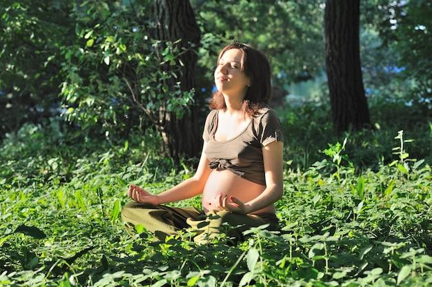아름 다운 임산부는 공원에 앉아 명상, 연꽃 포즈, 건강한 라이프 스타일
