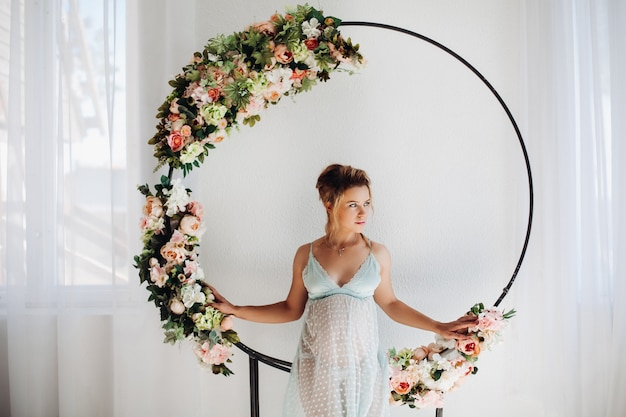 Beautiful pregnant woman in nighty dress posing inside decoration with flowers.