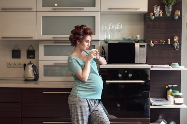 Beautiful pregnant woman relaxing at home with a cup of tea