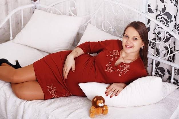 침대에서 쉬고 아름 다운 임신 한 여자