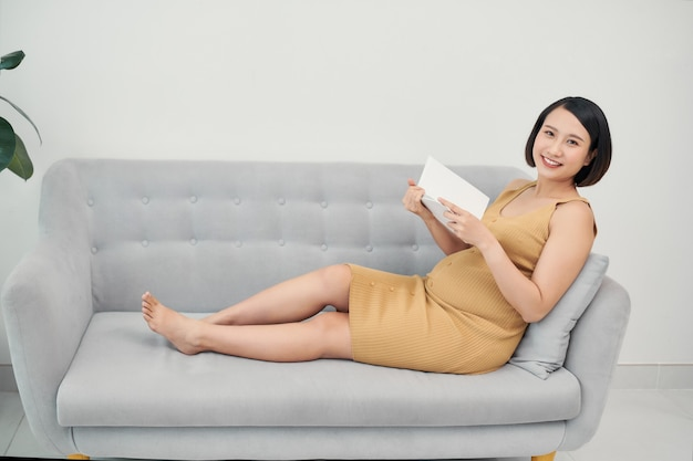 Beautiful pregnant woman resting and reading a book