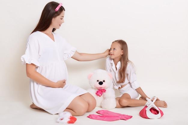 Красивая беременная женщина сидит с дочерью на полу в окружении детской одежды и мягкой игрушки