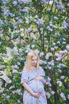 Beautiful pregnant woman smell flowering tree