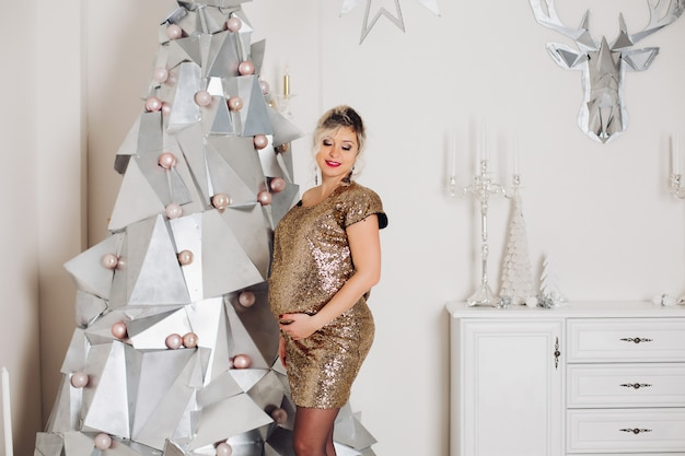 Beautiful pregnant woman in sparkling party dress at artificial modern christmas tree.