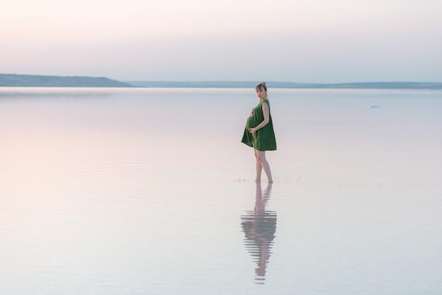 夕日の光線で水に立っている美しい妊婦。ビーチでの素晴らしい夜
