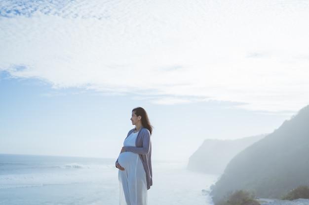 Красивая беременная женщина, стоя на пляже
