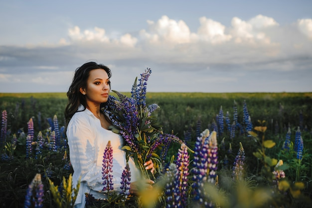 Beautiful pregnant woman stands among field of lupines on sky
