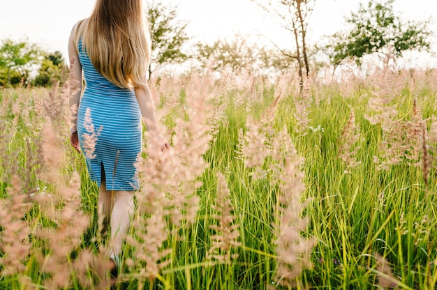 Beautiful pregnant woman in stylish summer dress go walking in  field with flowers in sunlight, enjoying feeling.