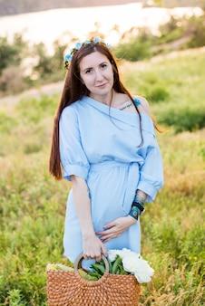 Красивая беременная женщина в голубом платье в цветущем саду