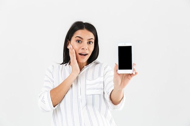 Красивая беременная женщина с большим животом улыбается и держит смартфон в руке, стоя изолированно над белой стеной