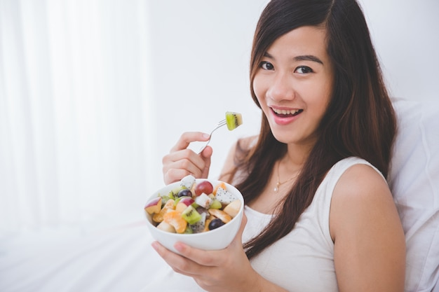Beautiful pregnant woman with a bowl of fruit